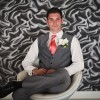 groom sitting on white chair before the wedding